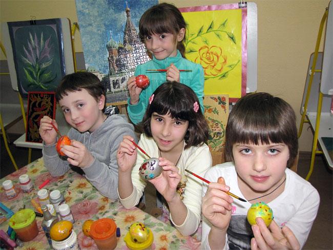 Дети красят пасхальные яйца