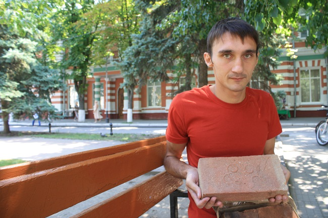 Азовский археолог Дмитрий Зенюк с кирпичами, где есть знаки староалбанского алфавита